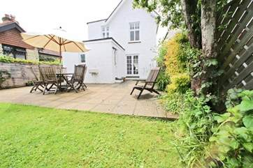 Pretty enclosed garden with patio and lawned areas