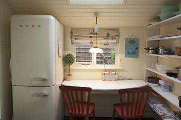 The utility area off of the kitchen has a small table for two. Perfect for eating those cupcakes you have perfected.