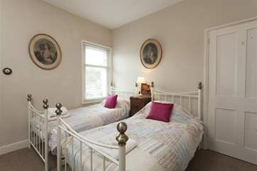 The twin bedroom has an old world feel to it with sturdy wrought iron bedsteads.