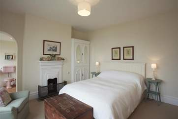 The master bedroom has a kingsize bed and archway to ensuite bathroom.