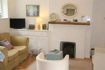 The cosy living room has an open fire.