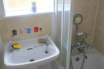The compact bathroom with shower attachment.