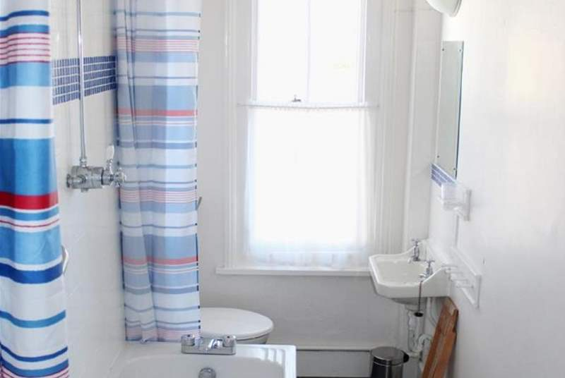 The bright bathroom with an overhead shower.