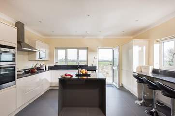 A spacious kitchen with breakfast-bar and central island completes this very stylish kitchen.