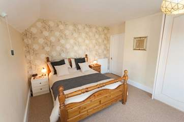 The main bedroom has gently sloping ceilings and is comfortably furnished