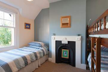This family bedroom has a set of bunks and a day bed, along with a pretty Victorian feature fireplace