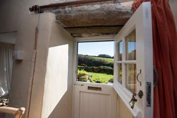 A stable door with a very low lintle leads to the garden and stream.