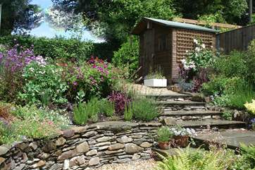 There is a gorgeous cottage garden at the back of the cottage. Stone steps lead up from the back door in the kitchen.