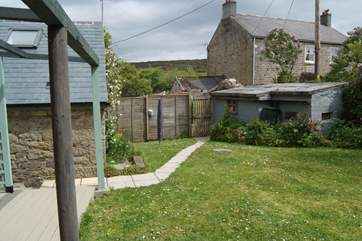 The garden runs alongside the cottage with the Owners farmhouse at the rear of the picture.