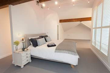 The spacious master bedroom is light and beautifully decorated