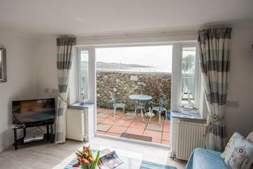 Patio doors lead outside to the walled terrace and the sound of the sea.