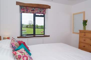 This is one of the three bedrooms, there are views out over fields and across the valley beyond.