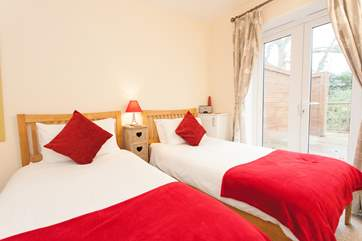 The twin bedroom is located on the ground floor with doors that can open up onto the private decking