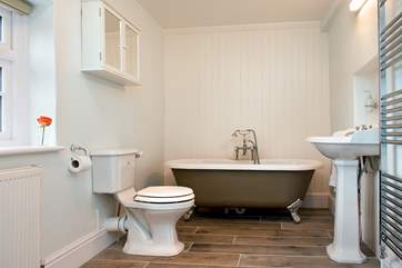 The very stylish cottage bathroom with a free-standing bath at one end....