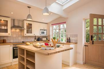 The lovely cottage kitchen is wonderfully light and  airy