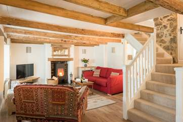 The comfortable sitting-area around the contemporary wood-burner with original beamed ceiling, if you are over 6ft tall you may need to duck and mind your head on the way up the stairs!