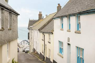 This pretty cottage with the blue door and windows sits on the hill close to the harbour, the pub and a short stroll to the beach,