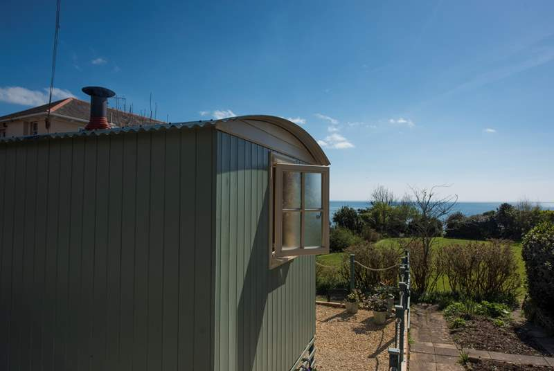 The shepherd's hut is in on an elevated deck, with views across Lyme Bay to Golden Cap in the distance.