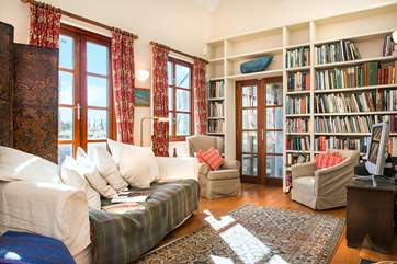 The double height second sitting-room is incredibly light and airy - with plenty of holiday reading and French doors leading out to the terrace.