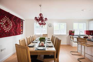 Cheeky red chandeliers hang over the dining-table.