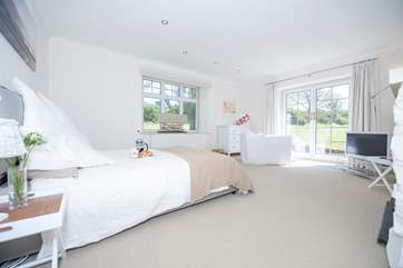 This ground floor bedroom has French windows which open onto the garden.
