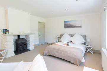 There's a wood-burner effect gas stove in this lovely ground floor bedroom.