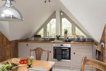 The kitchen is fitted between the sloping eaves - with a wide window again, looking out over countryside.