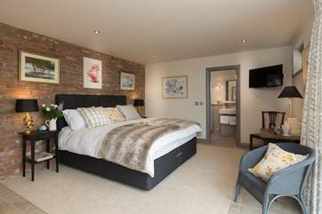 The stylish ground floor bedroom(bedroom 2) has a luxurious super king bed and an en suite, with bath and shower cubicle.