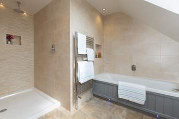 The en-suite for the first floor bedroom has a walk-in shower with a rainfall shower head, as well as a bath.