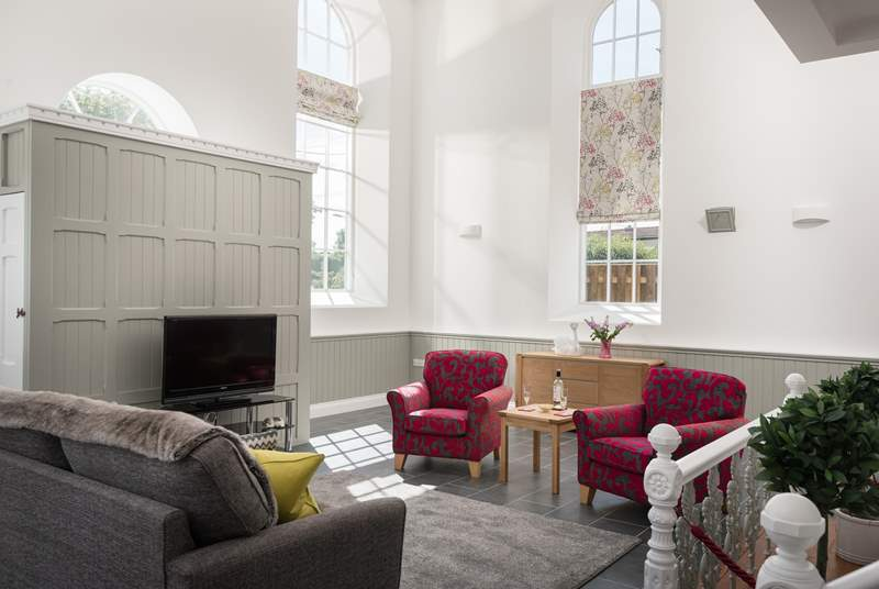 The sitting-area in the open plan living-room has tall arched windows and a high apex ceiling.
