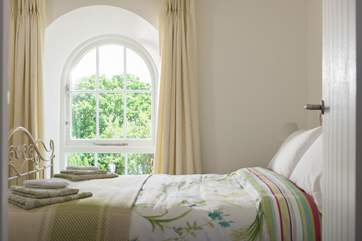 Another lovely arched chapel window allows light to pour into the bedroom.