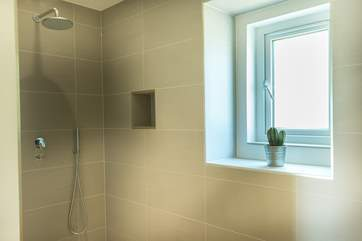 A big walk-in shower with drench-head shower.