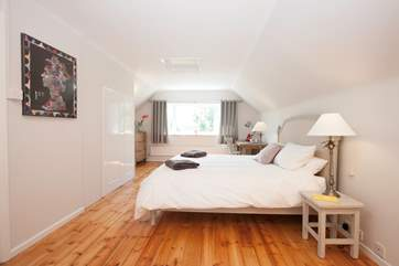 The master bedroom is certainly impressive in size and style with beautiful wooden floors adding to the charm
