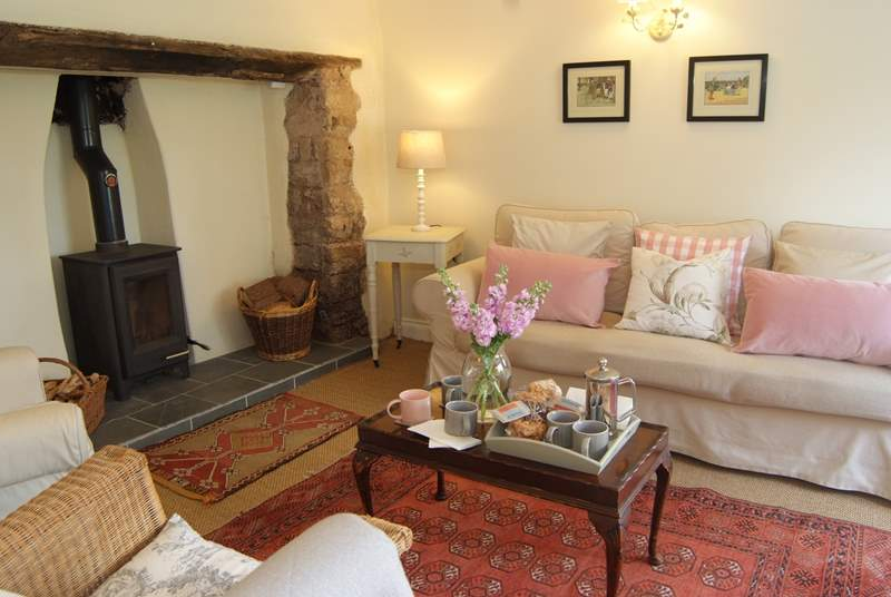 The wonderful welcoming living room has an inglenook fireplace and a wood burning stove.