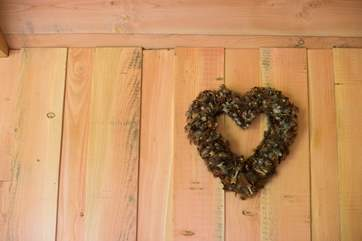 A heart-shaped pheasant feather wreath sits above the bed.