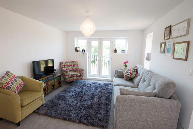 The stylish living room has ample seating for everyone to relax in comfort and has a door leading to the first floor balcony
