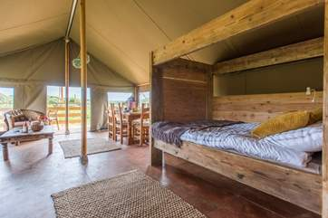 The delightful living area is open plan, complete with cosy cabin bed (Tembo will be similar to Twiga, the neighbouring safari tent pictured).