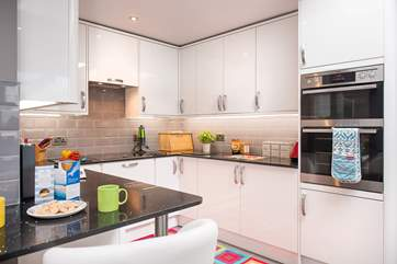 The contemporary kitchen has a little breakfast-bar, an ideal perch for breakfast or morning coffee, or to sit and keep the cook company.