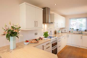 The delightful kitchen with double cooker and wine fridge is a beautiful space to cook and entertain the family