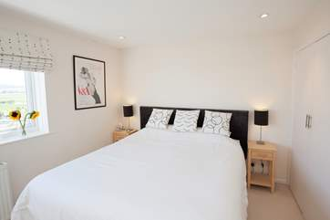 The master bedroom has a spacious super-king bed and beautiful views across the marshes and  harbour to wake up to