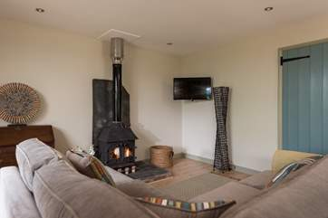 The wood-burner is perfect for cosy film nights, snuggled up on the big corner sofa.