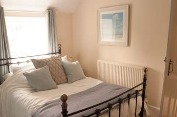 Bedroom 1 with a metal double bed and views over the garden.