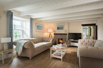 Two comfy sofas at one end of the living room are placed in front of the open fire.