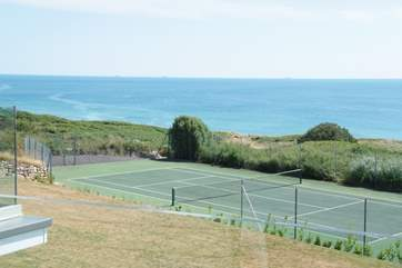 A view from the apartments across the gardens and the neighbours' tennis court to the beach beyond.
