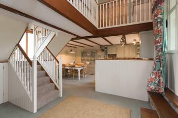 The staircase separates the living area from the kitchen/dining area.