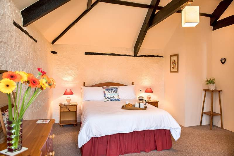 The bedroom retains much of the character of the original barn with stone walls and exposed beams.