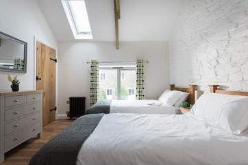 A floor to ceiling window and Velux roof window allow light to flood in during the day.