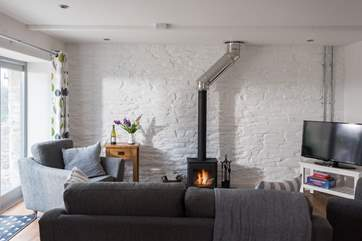 The wood-burner is a cosy focal point in cooler months.