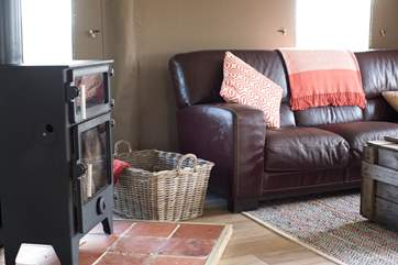 The spacious open plan living area comes complete with a cosy wood burnning stove that serves as an oven too.