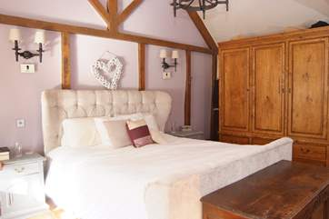 The bedroom is stylishly furnished and has plenty of storage and clothes hanging space.